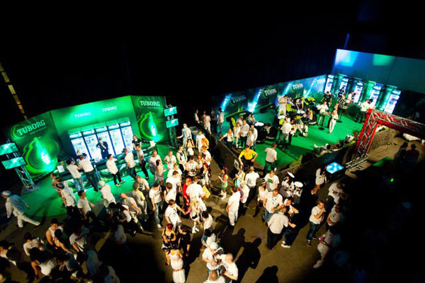 Lounge area with portable bars and music stage at a tuborg promotion event
