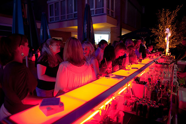 A group of ladies stands at a Justincase bar with orange lights on at a 28s Finest event in Germany