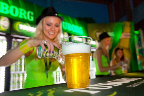 A bartender serving a beer in a tuborg promotion action