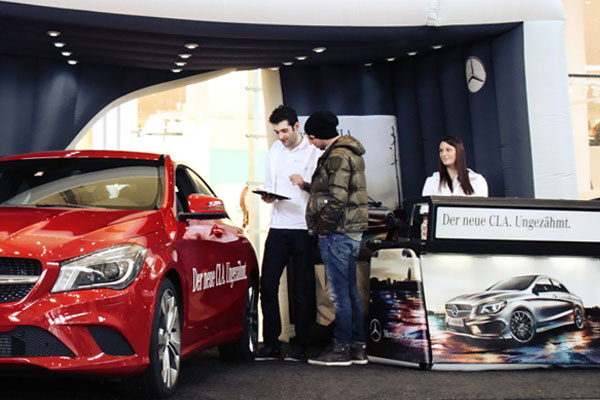 Car enthusiasts grabbing some information about the latest Mercedes-Benz car model