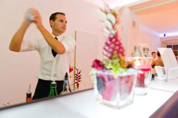 Mixologist prepares a cocktail while vigorously using a shacker