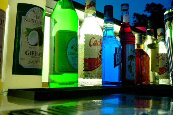 A line of bottles standing on top of a bar counter